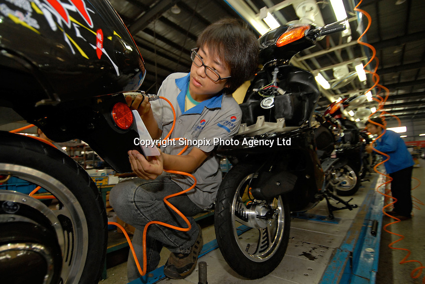 Workers inside a motorbike factory in Yixing city, China..20 Sep 2006