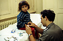 France 1989.Enfant kurde soigne par un medecin militaire au camp de Lastic.France 1989.Iraqi Kurdish child with a medical doctor in the camp of Lastic