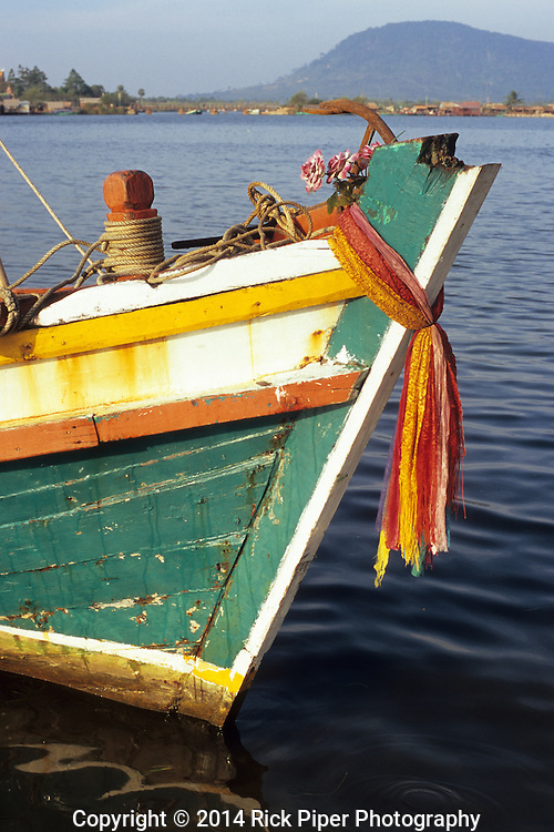 Prow of colourful traditional Cham fishing boat adorned with plastic flowers and scarves, at dawn on the Sanke river, Kampot, Cambodia