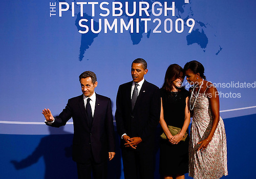 Pittsburgh, PA - September 24, 2009 -- United States President Barack Obama (2L) greets French President Nicolas Sarkozy (L) at the welcoming dinner for G-20 leaders as U.S. first lady Michelle Obama (R) and French first lady Carla Bruni Sarkozy talk with each other at the Phipps Conservatory on Thursday, September 24, 2009 in Pittsburgh, Pennsylvania. Heads of state from the world's leading economic powers arrived today for the two-day G-20 summit held at the David L. Lawrence Convention Center aimed at promoting economic growth.  .Credit: Win McNamee / Pool via CNP