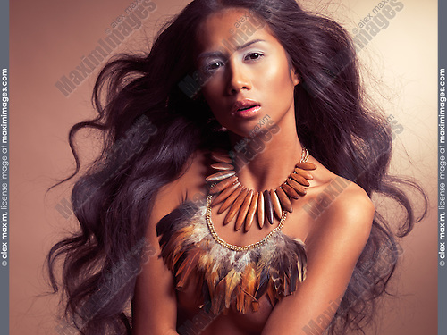 Ethnic beauty portrait of a young exotic woman with long beautiful flying hair wearing wooden and feather necklaces