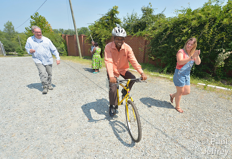 Casmil Ngundakumana, a refugee from Rwanda, rides a bike in Durham, North Carolina, on July 22, 2017. He gets help from Greg Garneau (left), a volunteer who coordinates the refugee bike program for the Durham Bicycle Co-op, and Monique Lohmeyer (right), a case manager for Church World Service. <br /> <br /> Church World Service resettles refugees in North Carolina and throughout the United States.<br /> <br /> Photo by Paul Jeffrey for Church World Service.