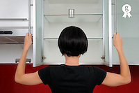 Woman looking inside an empty kitchen's cupboard (Licence this image exclusively with Getty: http://www.gettyimages.com/detail/102966068 )