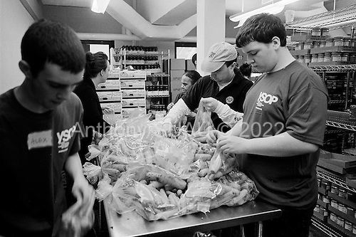 February 28, 2009.New York, New  York.USA..The Yorkville Common Pantry on a Saturday distributes food for free. The volunteers who work at the pantry see many new people coming as the economic crisis creates greater unemployed amongst the lower middle class in the United States. ..Volunteers prepare the food packages just before opening.