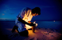 November 27th, 2008_MALDIVES_ A worker from the Soneva Fushi resort island in the Baa Atoll, Maldives, lights a torch in preparation for a cocktail party on a small sand island nearby.  Soneva Fushi is a leader in green practices and plans to be carbon neutral by 2010 by implementing projects such as a deep-sea water cooling system to replace it's traditional air conditioners.  Photographer: Daniel J. Groshong/Tayo Photo Group