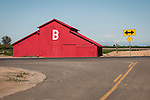 Freshly painted red barn with the letter B in California's San Joaquin Valley, double-arrow traffic sign
