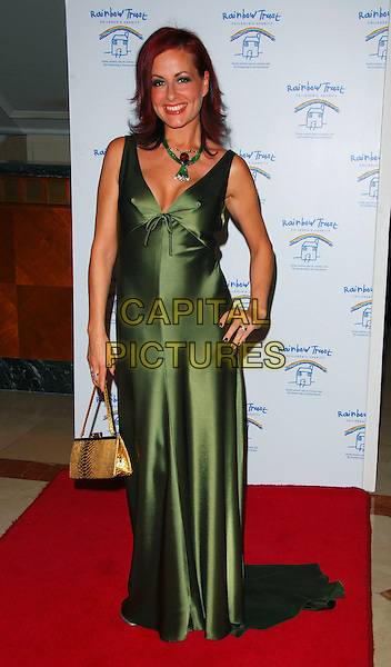 CARRIE GRANT.At The Rainbow Trust Ball, Park Lane Hotel,.London, England, November 11th 2006..full length green dress hand on hip.Ref: CAN.www.capitalpictures.com.sales@capitalpictures.com.©Can Nguyen/Capital Pictures