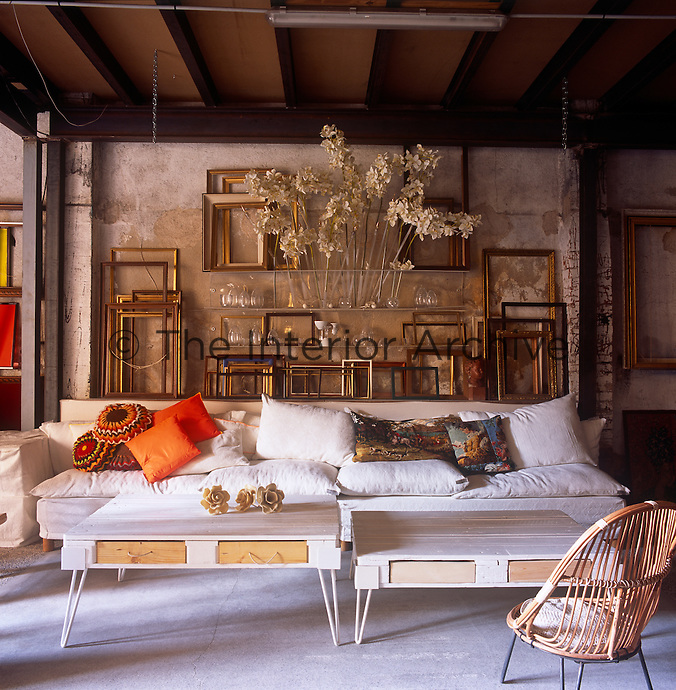 A country living room with distressed stone walls and a beamed ceiling. A collection of empty picture frames are arranged against one wall. Two painted tables stand in front a white sofa, while a splash of colour is provided by two orange cushons.