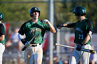 Dartmouth Big Green shortstop Nate Ostmo (5) fist bumps Matt Feinstein (23) after scoring a run during a game against the Northeastern Huskies on March 3, 2018 at North Charlotte Regional Park in Port Charlotte, Florida.  Northeastern defeated Dartmouth 10-8.  (Mike Janes/Four Seam Images)