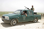Iraqi soldiers pass through a coalition forces engineering project in the Rumaylah Oilfields with a machine gun armed Mazda pickup truck.