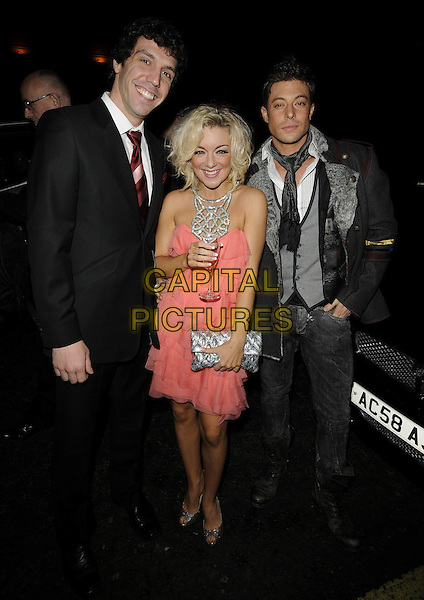 ALEX GAUMOND, SHERIDAN SMITH & DUNCAN JAMES.The Gala Performance of 'Legally Blonde' at The Savoy Theatre, London, England. .January 13th, 2010 .full length black suit grey gary red tie jeans boots brown scarf peach pink ruffle ruffles dress glass drink cast silver neck cut out clutch bag peep toe shoes champagne flute tiered halterneck waistcoat jacket.CAP/CAN.©Can Nguyen/Capital Pictures.