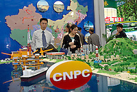 Visitors look at the map which locates the pipes that transports the gas from the west to the east, and a model of oil fields of China National Petroleum Corporation (CNPC), in the 2004 Shanghai International Industrial Fair. Shanghai, China. The 550 km railway is one of the China Significant Achievements in Engineering..