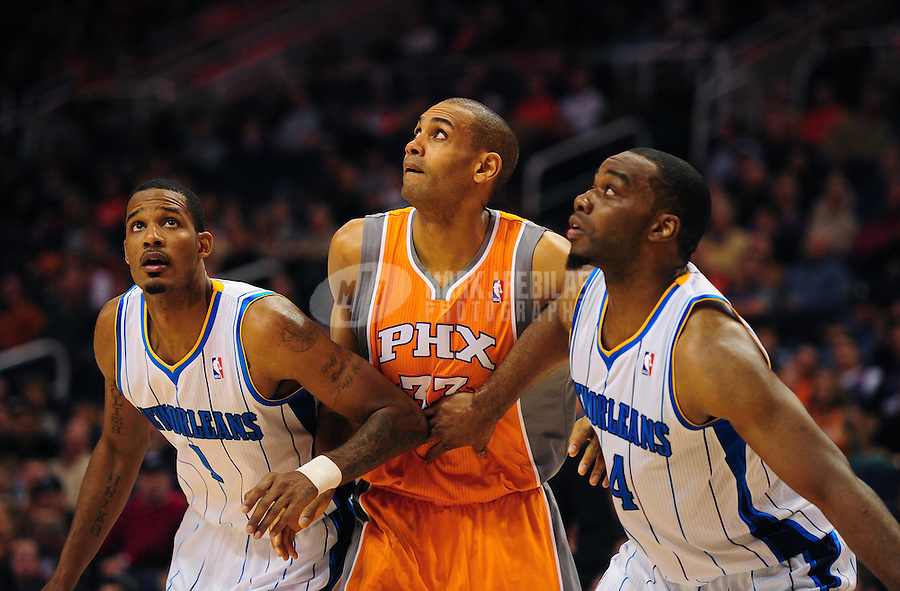 Dec. 26, 2011; Phoenix, AZ, USA; New Orleans Hornets guard/forward Trevor Ariza (1) and forward Carl Landry (24) surround Phoenix Suns forward Grant Hill as they position for a rebound at the US Airways Center. The Hornets defeated the Suns 85-84. Mandatory Credit: Mark J. Rebilas-USA TODAY Sports