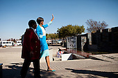First Lady Michelle Obama waves to onlookers after placing a wreath at the Hector Pieterson Memorial in Soweto, South Africa, June 22, 2011. The First Lady walks with Antoinette Sithole, Hector Pieterson's sister. .Mandatory Credit: Samantha Appleton - White House via CNP