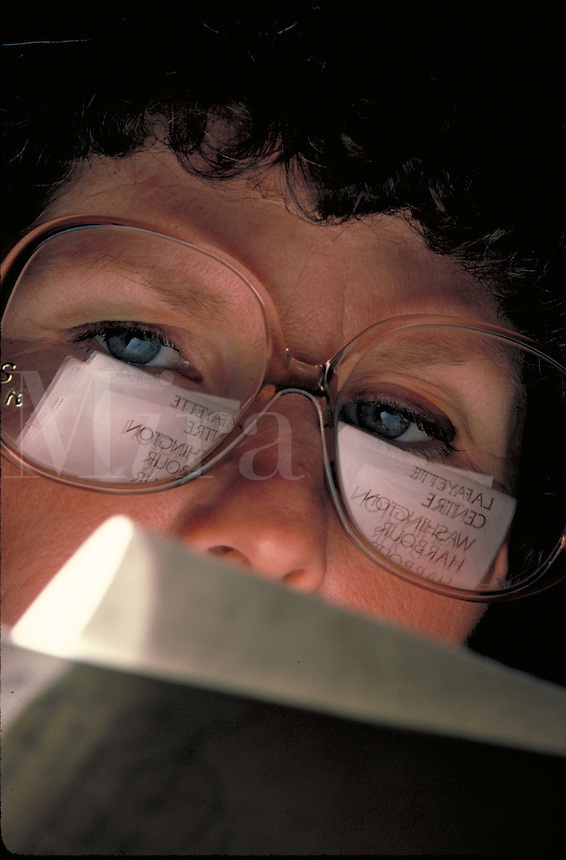 Woman reading copy; proofreading, portrait, close-up, business.