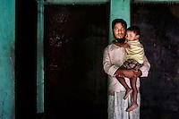 MD. Saddam Hossain holds his son Mizanur Rahaman and poses for a portrait in front of the living room in which his wife Mitu Begum (20) died due to the Tazreen Fashions factory fire in Ashulia, Bangladesh.