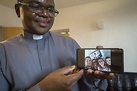 "Switzerland. Canton Ticino. Grancia. Reverend Father Gerald Chukwudi Ani did celebrate the Sunday mass at home and transmit it live on YouTube. Don Gerald Chukwudi Ani, originally from Nigeria, is a catholic priest from the Diocese of Lugano. On his Samsung smartphone, after the end of mass, he has received a picture taken by the Pozzoli family ( Left to right: Luca, Valeria, Martina and Andrea). The family took a selfie at home with the priest on television. Due to the spread of the coronavirus , the Federal Council has categorised the situation in the country as ""extraordinary"". It has issued a recommendation to all citizens to stay at home, especially the sick and the elderly. From March 16 the government ramped up its response to the widening pandemic, ordering the closure of bars, restaurants, sports facilities and cultural spaces. Celebrating masses is prohibit in order to avoid people meeting together. A selfie is a self-portrait digital photograph, typically taken with smartphone held in the hand. YouTube is an American online video-sharing platform. Grancia is a municipality in the district of Lugano in the canton of Ticino in Switzerland. 29.03.20 © 2020 Didier Ruef"