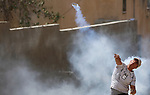 A Palestinian protester throws back a tear gas canister fired by Israeli forces during clashes following a weekly demonstration against the expropriation of Palestinian land by Israel in the village of Kfar Qaddum, near the West Bank city of Nablus on September 7, 2018. Photo by Shadi Jarar'ah