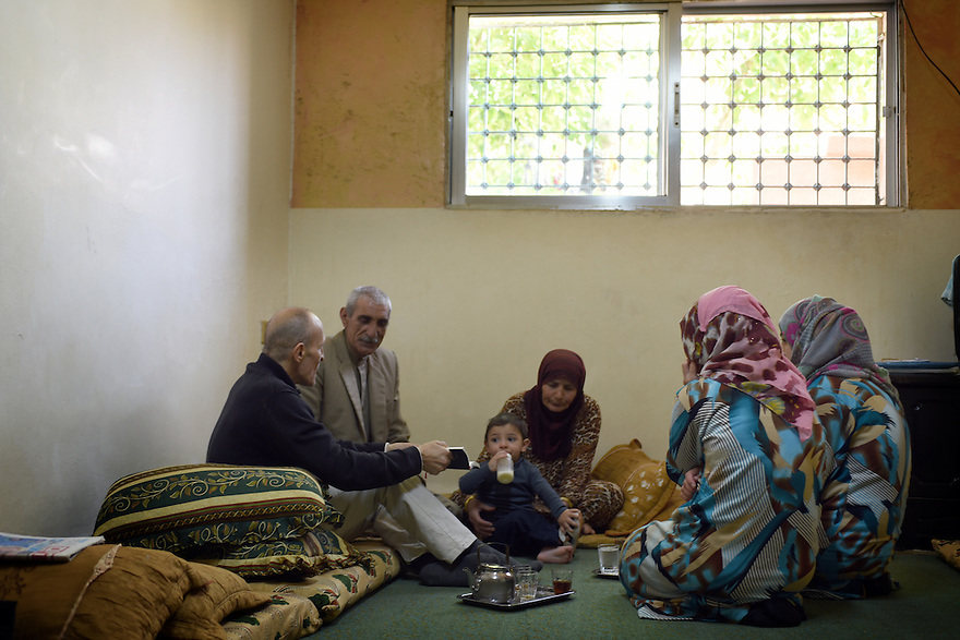 AMIN AHMAD MASH-HOON, 54, AND HIS FAMILY FROM HOMS, SYRIA SIT WITH PASTOR AMJAD IN THEIR NEW HOME IN MADABA, JORDAN. 20/04016. PHOTO CLARE KENDALL.