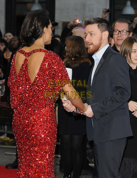 Rosario Dawson & James McAvoy.'Trance' World premiere held at Odeon West End, London, England..19th March 2013.half length red dress beads beaded sequins sequined side profile beard facial hair black suit blue shirt mouth open holding hands .CAP/CAN.©Can Nguyen/Capital Pictures.