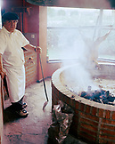 ARGENTINA, Patagonia, portrait of chef grilling lamb in Llao Llao Lodge hotel.