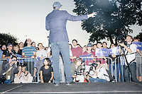 """Entrepreneur and Democratic presidential candidate Andrew Yang speaks to a large crowd in Cambridge Common near Harvard Square in Cambridge, Massachusetts, on Mon., September 16, 2019. Yang's unlikely presidential bid is centered on his idea for a """"Freedom dividend,"""" which would give USD$1000 per month to every adult in the United States. After appearing in three Democratic party debates, Yang has risen in polls from longshot candidate to within the top 10.   In the picture, people can be seen holding MATH signs or wearing hats that say MATH. The slogan MATH is now said to mean """"Make America Think Harder"""" and the candidate frequently sites statistics and mathematics in his speeches."""
