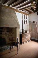 A massive stone fireplace dominates this living room where contemporary seagrass echoes the rush matting of a bygone era