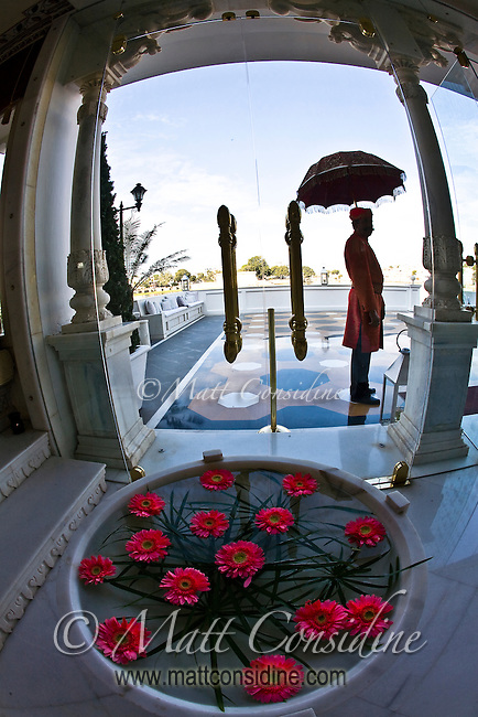 Silhouette of doorman in traditional costume with parasol at the Taj Lake Palace.<br /> (Photo by Matt Considine - Images of Asia Collection)