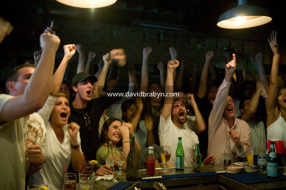 Supporters of the French rugby team react to a French try during France's surprise victory against New-Zealand in the quarter finals of the 2007 Rugby World Cup shown on a television screen (not pictured) in a French bar in the Lower East Side of Manhattan in New York, USA, 6 September 2007.