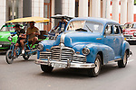 Havana, Cuba; a classic blue 1947 Oldsmobile car driving down the street in Old Havana