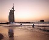 UNITED ARAB EMIRATES, Dubai, Burj Al Arab Hotel, surfers walking on beach with the Burj Al Arab Hotel in the background at sunset