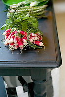Bunches of fresh radishes on a tabletop in the kitchen