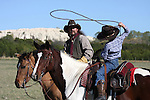 A young cowboy shows his dad how well he his throwing the rope while his horse watches on as well
