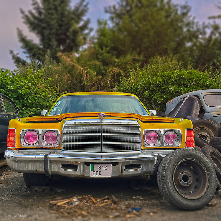 Old yellow classic Chrysler car in salvage area in USA with spare wheels