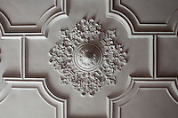 The ceiling of the dining room, which was originally the entrance hall of the house, is covered with ornate plasterwork