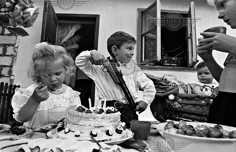 Children eat cake and play with toy guns at a birthday party in Sevastopol.