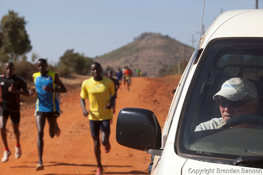 Renato Canova coaches elite Kenyan runners in the high altitude town of Iten. Here he monitors times from his pace car during a training run outside Iten, Kenya.