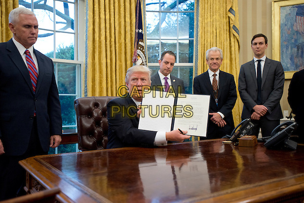 United States President Donald Trump shows the Executive Order withdrawing the US from the Trans-Pacific Partnership (TPP) after signing it in the Oval Office of the White House in Washington, DC on Monday, January 23, 2017.  The other two Executive Orders concerned a US Government hiring freeze for all departments but the military, and &quot;Mexico City&quot; which bans federal funding of abortions overseas.  Standing behind the President, from left to right: US Vice President Mike Pence; White House Chief of Staff Reince Preibus; Peter Navarro, Director of the National Trade Council; and Jared Kushner, Senior Advisor to the President.<br /> CAP/MPI/CNP/RS<br /> &copy;RS/CNP/MPI/Capital Pictures