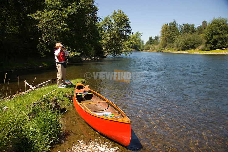Man Standing on the Banks of the Santiam River with Canoe