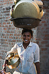 Young Gujarat woman carrying a big load of cleaned dishes on her head, Gujarat, India --- Model Released