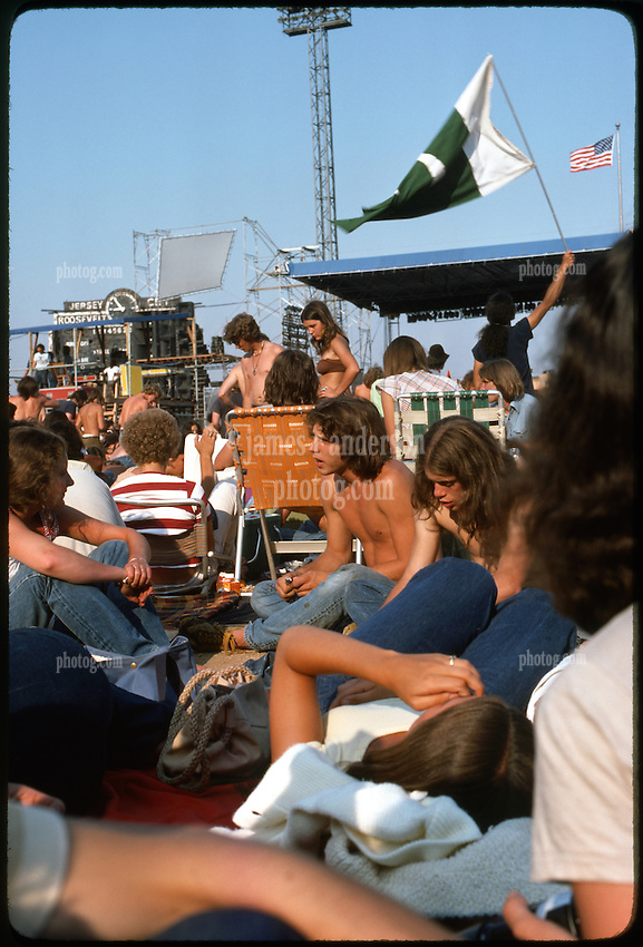 Waving that Flag. The crowd chillaxing in the hot late day sun before the Grateful Dead Concert begins at Roosevelt Stadium 4 August 1976. Parts of the stage, sound & lights booth and the decaying Roosevelt Stadium Scoreboard in the distance.