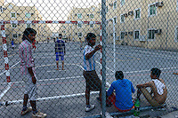 QATAR, Doha, housing complex for migrant worker outside the city, sports place / KATAR, Doha, Gastarbeiter, Sammelunterkunft fuer Gastarbeiter ausserhalb der Stadt, Sportplatz, Gastarbeiter aus den Philippinen und Vietnam spielen Fussball