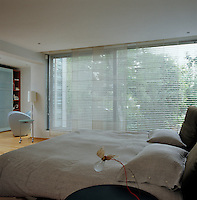 Transluscent blinds hang against the large picture window in the master bedroom