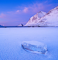 Block of ice on frozen Haukland beach in winter, Vestvagøy, Lofoten islands, Norway
