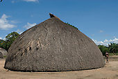 Xingu Indigenous Park, Mato Grosso State, Brazil. Aldeia Kamaiura. Exterior of traditional oca house showing end view.