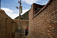A woman walks in an alleyway between houses in Xiahe, Gansu, China. Xiahe, home of the Labrang Monastery, is an important site for Tibetan Buddhists.  The population of the town is divided between ethnic Tibetans, Muslims, and Han Chinese.