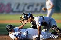 July 7, 2009: Tri-City Dust Devils catcher Jose Gonzalez couldn't come up with the throw from the outfield as Salem-Keizer Volcanoes' Drew Biery slides into home plate.