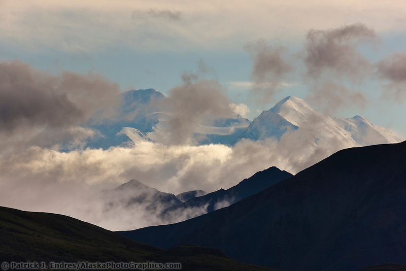 The North and South summits of Denali, North American's tallest mountain, are visible through partly cloudy skies in Denali National Park, Interior, Alaska.