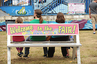 NWA Media/ANDY SHUPE - Fairgoers sit on a bench in the midway Saturday, Aug. 30, 2014, at the Washington County Fair in Fayetteville. The fair concluded Saturday.