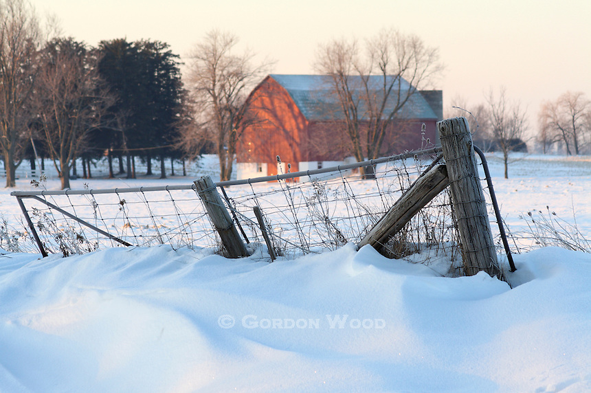Farm Gate Fence and Barn in Snowy Field